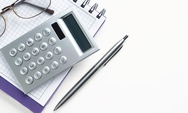 Калькулятор и очки на открытом блокноте. рядом с ним есть ручка.