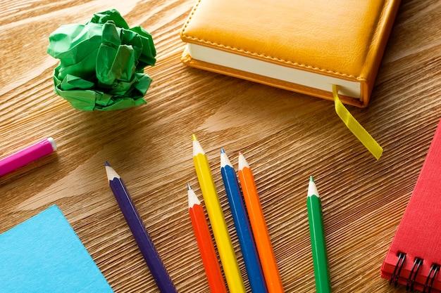 色のマーカーと鉛筆、木製のテーブルの描画パッド。
