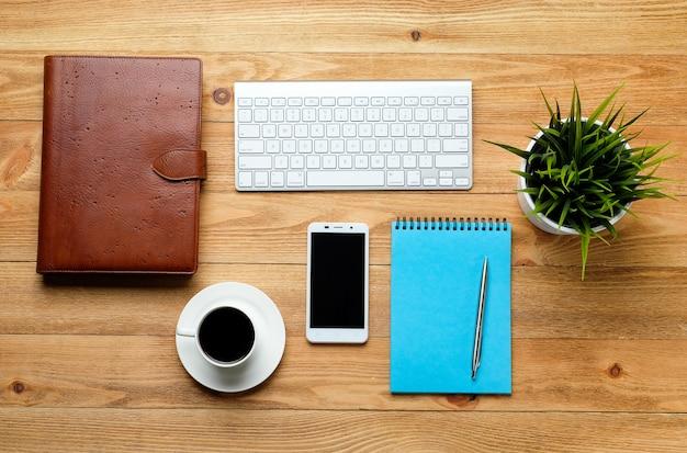 Мобильный телефон, клавиатура компьютера, ручка и блокнот для заметок, кружка кофе и цветок на деревянный стол.