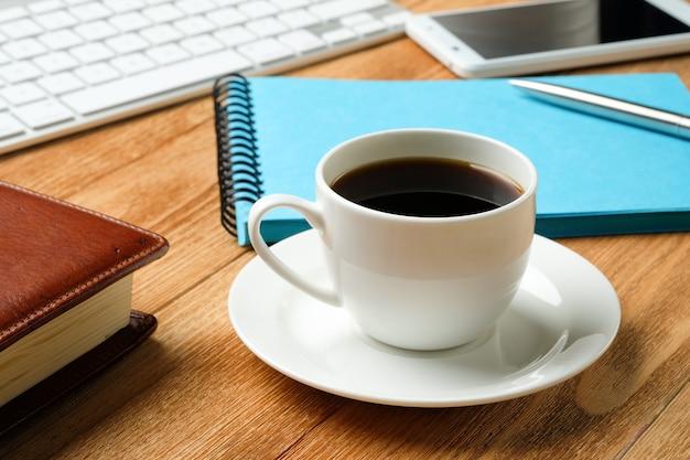 携帯電話、コンピューターのキーボード、ペン、メモ用のメモ帳、木製のテーブルの上のコーヒー・マグ。