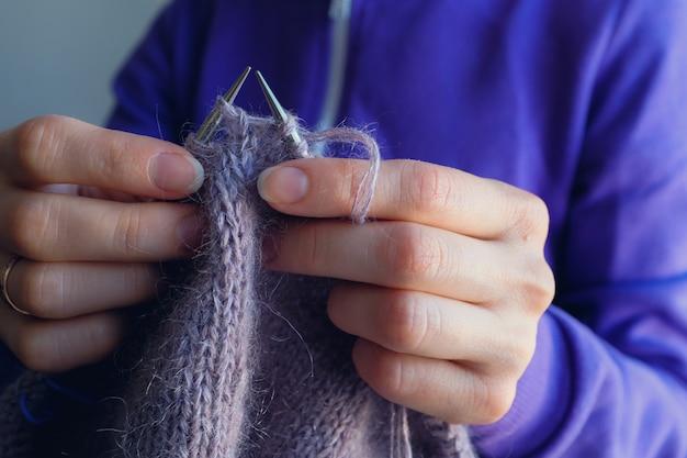 女性はウールの服を編みます。編み針閉じる。天然ウール