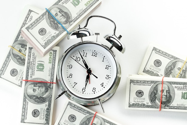 Блестящий железный будильник и стопки бумажных долларов