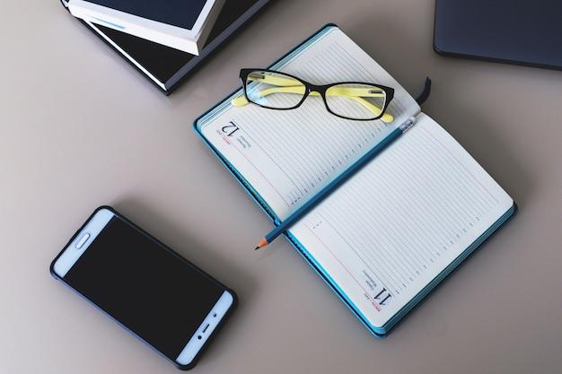 ノートとペンとメガネの本はテーブルの上にあります。教育。ビジネス。作業。