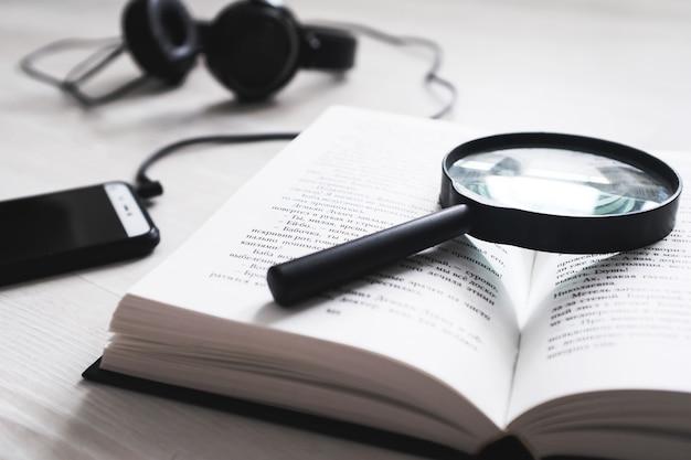 Книга и лупа на белом, рядом лежат телефон и наушники.