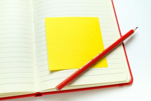 開いたメモ帳の空白ページの情報を鉛筆で思い出させるための黄色のステッカー