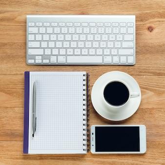 Мобильный телефон, клавиатура компьютера, ручка и блокнот для заметок, кружка кофе, на деревянном столе. темы работы бизнесмена или менеджера на рабочем месте.