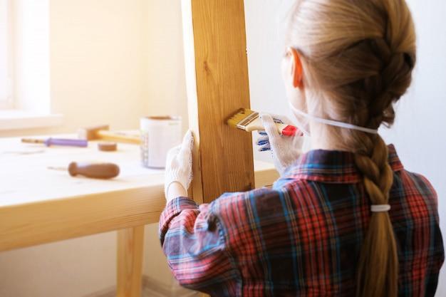 修理工、大工、雇われた労働者は木の板に保護ニスまたはペイントブラシを塗ります。手袋を手でペンキでブラシを保持しています。家および専門家の修理、建設の概念。