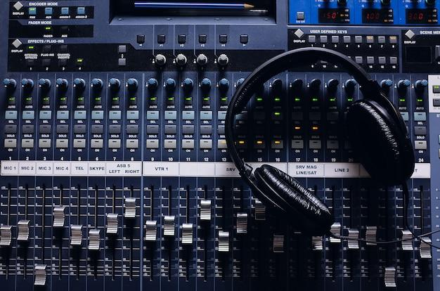 Наушники, усилительное оборудование, ручки студийного микшера и фейдеры. звуковое оборудование. выборочный фокус. фотография покрыта песком и шумом.