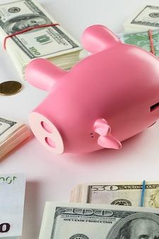 白の束でドル札とユーロ。近くにはさまざまな国の硬貨があります。ピンクのブタの形の貯金箱。