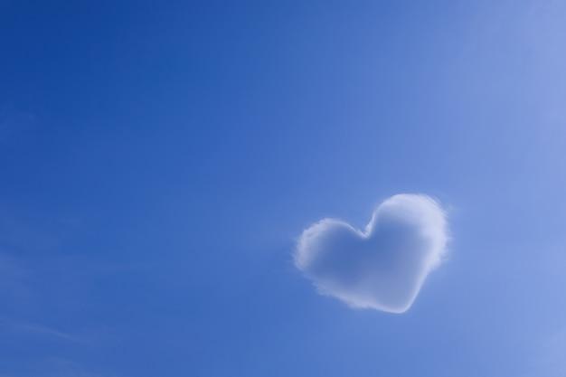 美しいのどかな青い空、愛のシンボルに対するハートの形をした白い雲。想像力、バレンタインデーの背景の概念