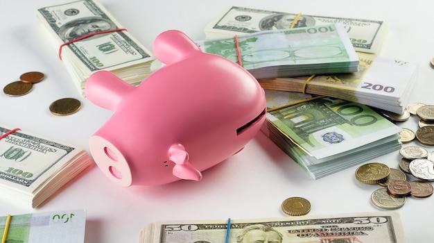 白い表面の束のドル札とユーロ。近くにはさまざまな国の硬貨があります。ピンクのブタの形の貯金箱。