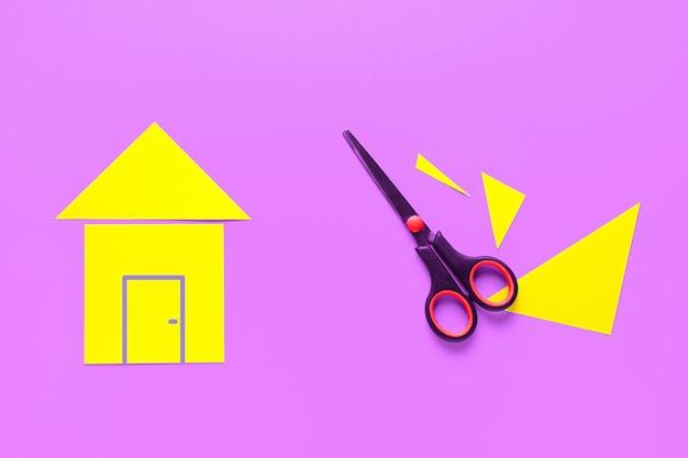明るいピンクの背景に色紙を切り取った家。近くにハサミがあります。