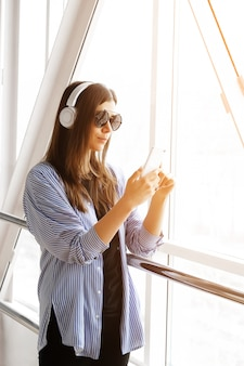 自信を持って女の子またはヘッドフォンで音楽を聴く、部屋、空港、オフィスで電話を見ているフリーランサー。メガネでスタイリッシュなおしゃれな若い女性の手の中に携帯電話。