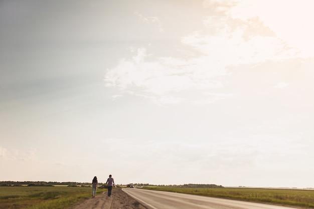 愛のカップルは田舎道です。ヒッチハイクの概念背面図テキスト用のスペースをコピーします。
