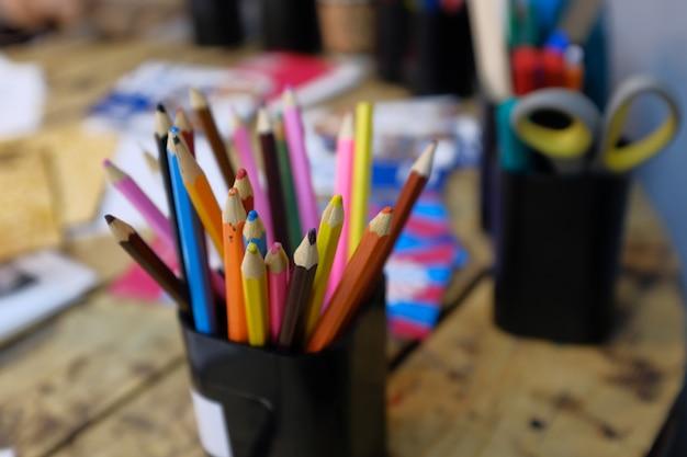 木製のテーブルの上のスタンドに色鉛筆。絵の学校、子供の創造性。