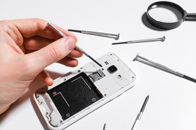 携帯電話の修理、手のクローズアップ
