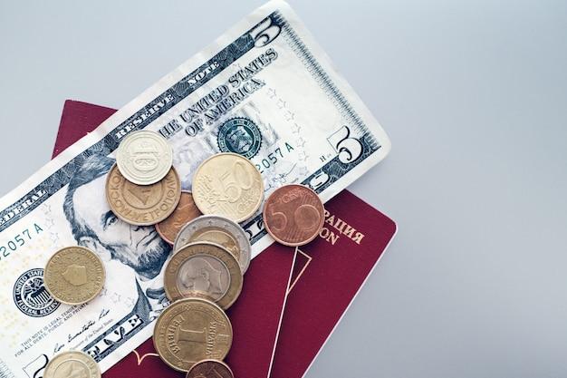 Паспорт с банкнотами и монетами на простой фон.