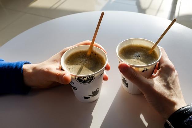 Мужские руки держат бумажные одноразовые чашки кофе на столе в кафе.