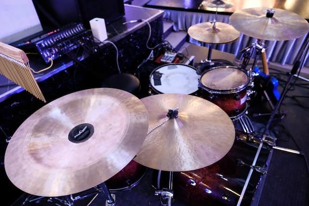 バックグラウンドでフォーカス楽器部品から設定ドラムのゴールデンブロンズシンバルプレート部分のクローズアップ