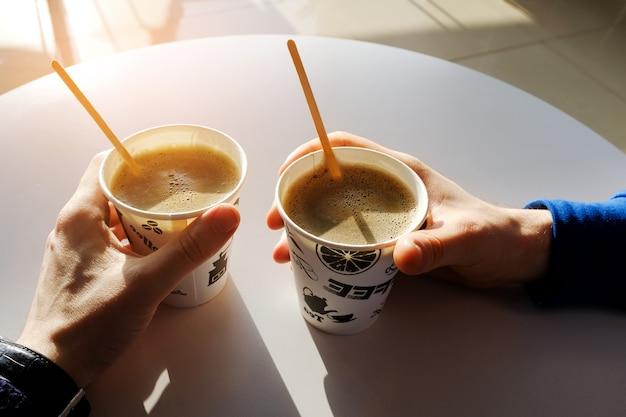 カフェの白いテーブルの上の紙の使い捨てコーヒーカップを保持している男性の手