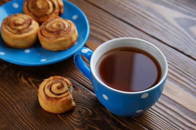 自家製シナモンロールは木製のテーブルの上の青い皿の上にあります。