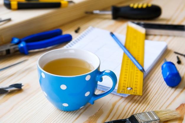 家やアパートの改修を構築するためのマグカップ、図面および構築ツール。