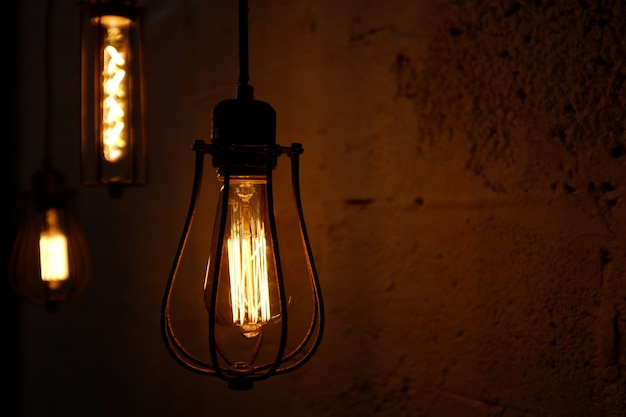 Стеклянная ретро лампа эдисон на темном фоне.