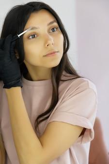 Молодая женщина в перчатках расчесывает брови в салоне красоты