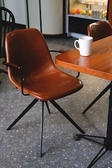 カフェの木製のテーブルの上のコーヒーや紅茶の白いマグカップ。