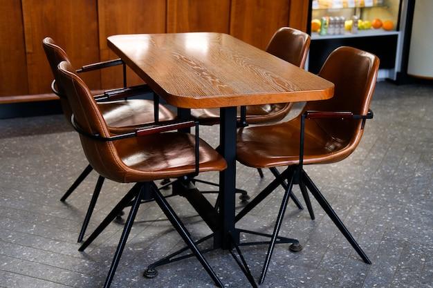 カフェ、オフィス、または部屋にある木製のテーブルと革張りの椅子または椅子。