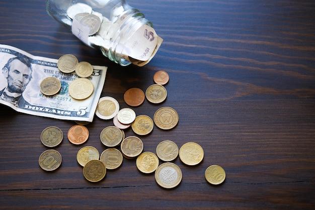 Банкноты, доллары и монеты разных стран на фоне деревянного стола.