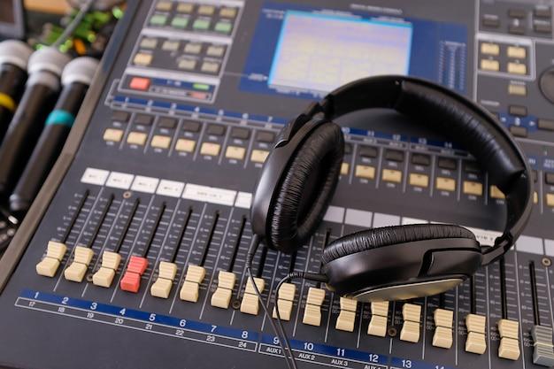 ヘッドフォン、マイク、増幅装置、スタジオオーディオミキサーのノブとフェーダー。