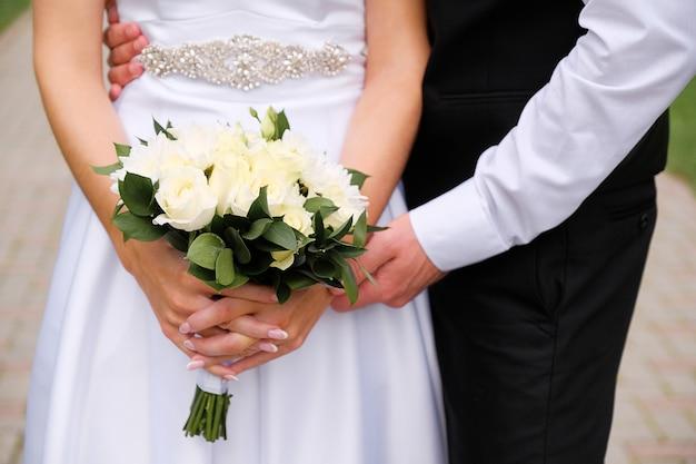エレガントなウェディングドレスの花嫁は、白いバラと菊の花と緑の葉の美しい花束を持っています。新婚夫婦、新郎新婦のクローズアップの手、屋外で抱きしめます。