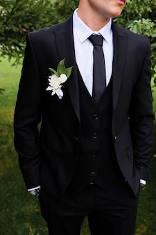 白いシャツ、ネクタイ、黒または紺色のスーツの新郎は目をそらします。白いバラや菊の花の美しいブートニエールと彼のジャケットの襟の上の緑の葉を持つ若者。結婚式のテーマ