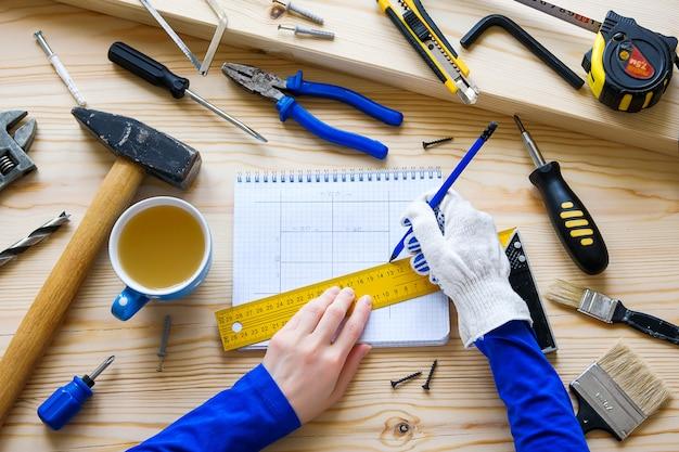Руки плотника, чертеж строительного или ремонтного проекта.