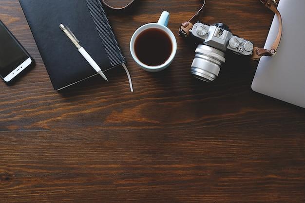 一杯の紅茶、カメラと暗い木製のテーブルの上のノート。写真家やフリーランサーの職場。トップビューの背景