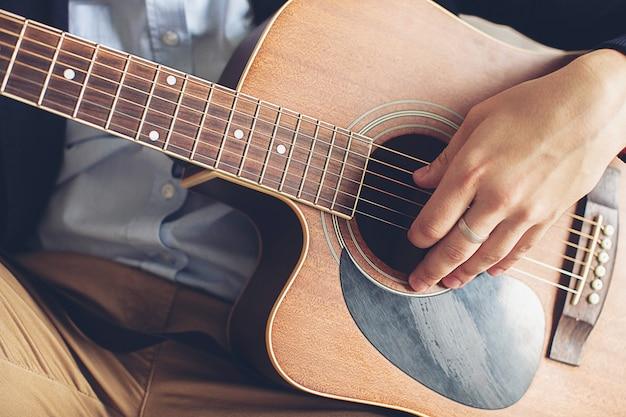 青いシャツ、濃い青のジャケット、茶色のズボンでギターを弾くスタイリッシュでファッショナブルな男。趣味、情熱、そして音楽への関心の概念。手の男は、ギターの弦に触れるクローズアップ。
