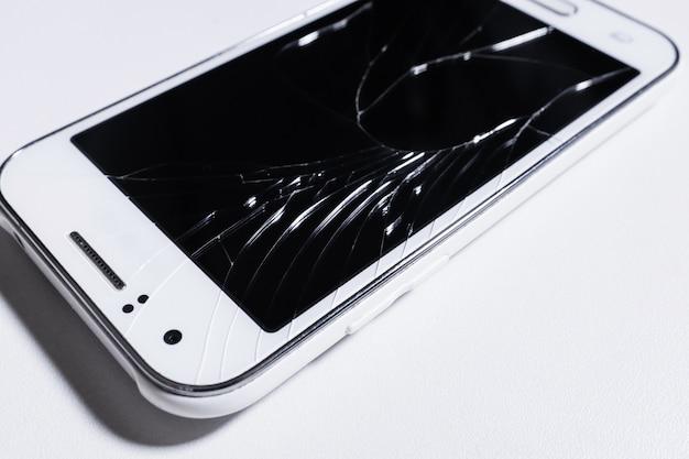 白い携帯電話の壊れた画面
