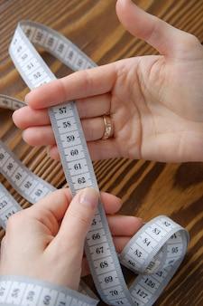 女性の手持ち株測定テープ木製の背景に。