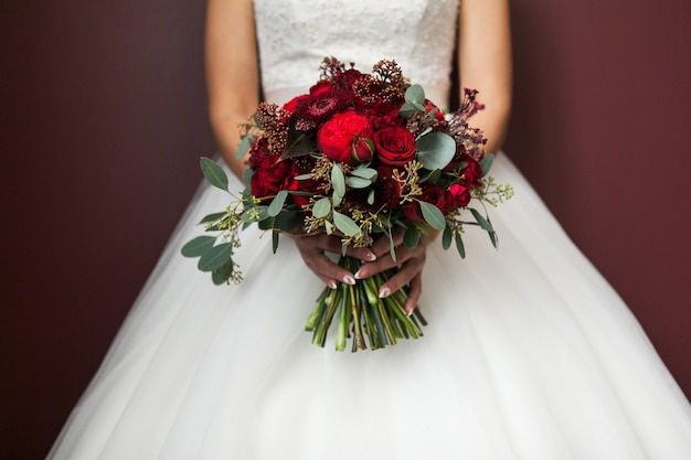 ウェディングブーケを持って白のエレガントなウェディングドレスの花嫁。