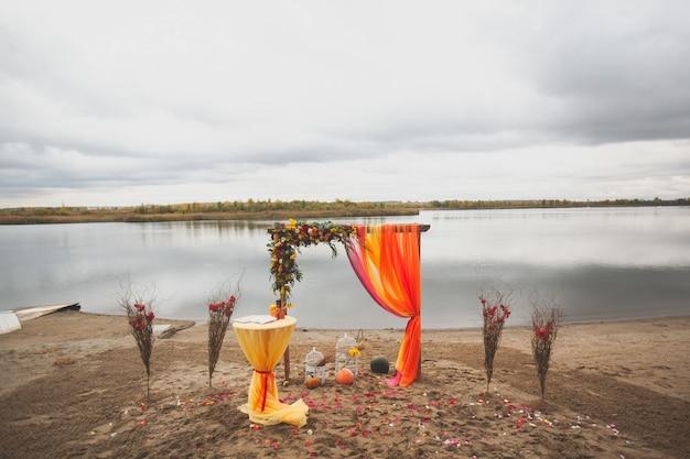 砂浜のビーチで花と布の結婚式のアーチ。結婚式の装飾