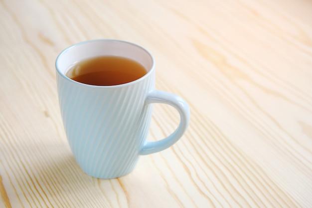 木製のテーブルのクローズアップに紅茶のマグカップ。
