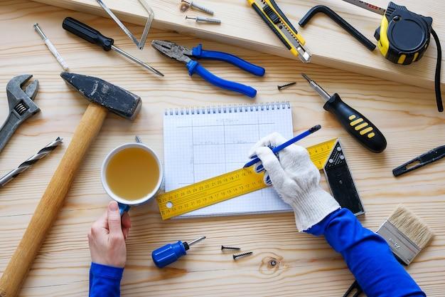 Блокнот с чертежами и строительными инструментами. в руках женщины чашка чая и карандаш.
