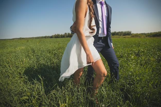 背の高い緑の芝生で新郎新婦。夏の公園を歩いている男と女。