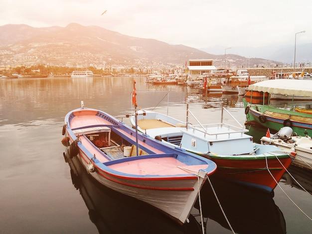 美しい景色。港と街と山々に面した小さなボートがあります。