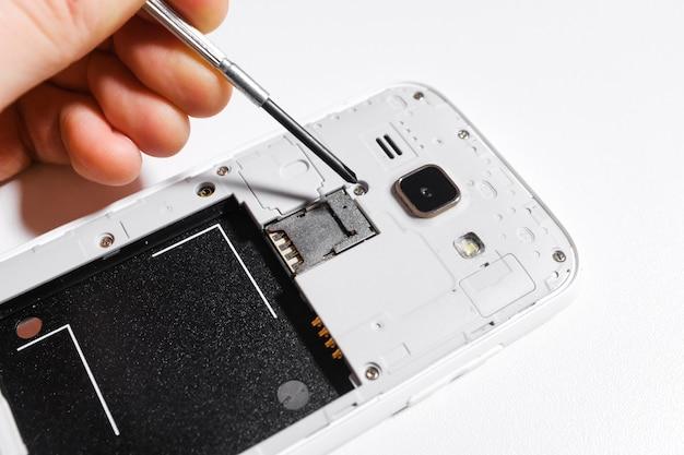 携帯電話の修理、分離白の手のクローズアップ