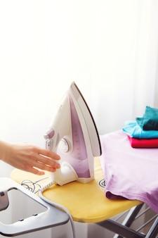Женщина-домохозяйка глажка одежды в домашних условиях. женская рука утюг.