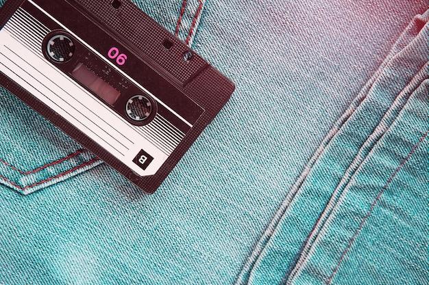 Винтажная ретро аудиокассета на фоне зеленых джинсов