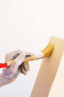 修理工、大工、保護手袋の勤勉な労働者が木の板にブラシでニスを塗ります。