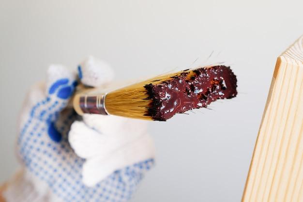 修理工、大工、勤勉な労働者は木の板に保護ニスまたは塗料を塗布します。